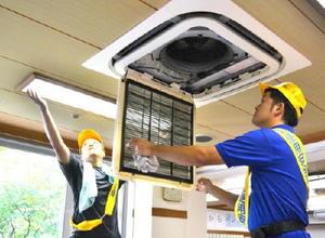 蛍光管やエアコンのフィルターを取り外し、清掃する鳥栖電気工事業協同組合のメンバー=みやき町簑原の夢の里