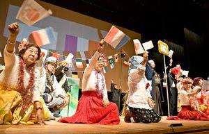 日仏の国旗を振って劇を盛り上げる学生=佐賀市文化会館