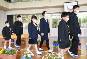 緊張した表情で入学式に臨む新入生たち(手前の3人)=唐津市の伊岐佐小