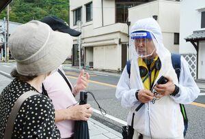 フェイスシールドをつけて観光案内するガイドの岩崎数馬さん=有田町幸平