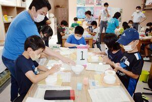 北川朝行さん(左)の指導で、石こう型に陶土を詰めて箸置きを作る児童たち=有田町泉山の体験工房ろくろ座