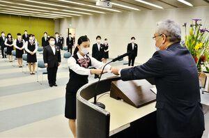 坂井秀明頭取(右)から辞令を受け取る新入行員の代表者=佐賀市の佐賀銀行本店