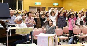 ステージ上のスタッフを見ながら、ピアノの伴奏に合わせて体操する参加者=佐賀市のエスプラッツホール