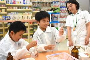 計量し水薬を作る児童=佐賀市の溝上薬局高木瀬店