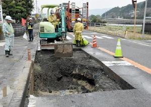 陥没した国道202号の路面で、周囲のアスファルトを取り除いて復旧作業をする人たち=伊万里市二里町中里