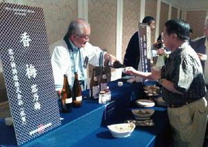 参加者に大吟醸酒を注ぐ窓乃梅酒造の古賀醸治社長(左)=宮崎市の宮崎観光ホテル