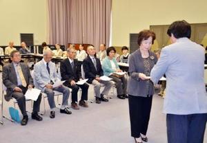 委嘱書を松田一也町長から受け取る民生委員児童委員協力員の女性=基山町民会館