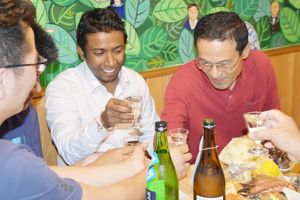 佐賀のお酒で乾杯する留学生ら=佐賀市のゲストハウス「HAGAKURE」