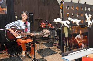 タブレット端末を使い、店内で動画を撮影している苣木孝文さん=唐津市中町の音楽酒場「明日があるさ」