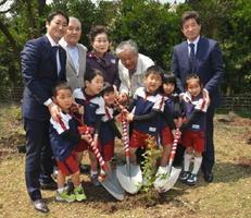 境町の行政関係者や住民と共に、ブルーベリーの苗木を植樹する園児たち=みやき町白壁の四季彩の丘みやき
