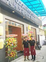 一吉うどんのベトナム支店の前で笑顔を見せる轟木一弘代表(左)=ベトナム・ホーチミン市