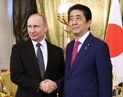 ロシアのプーチン大統領(左)と握手する安倍首相=27日、モスクワ(共同)