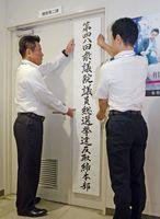 第48回衆院選の選挙違反取締本部の看板を設置する捜査2課の木下浩一次席(左)ら=佐賀市の佐賀県警本部