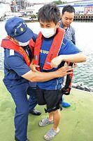 海上保安官からライフジャケットの着方を学ぶ教員=唐津市二タ子