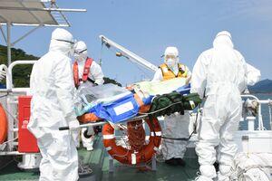 感染防止具に覆われた模擬感染者を船から運び出す救急隊員ら=唐津市の唐津東港
