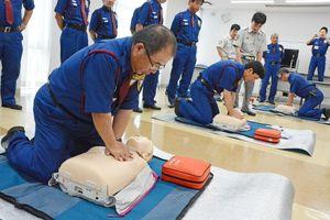 消防局の指導の下で人形に心臓マッサージを行う中央警備保障の社員たち=佐賀市の同社本社
