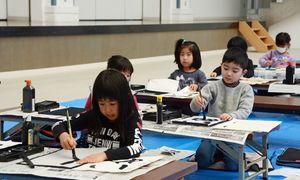 真剣な表情で筆を動かす参加者=有田町の〓の博記念堂