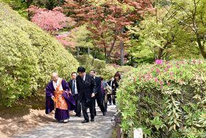 開き始めたツツジを楽しみながら園内を散策する出席者=基山町の大興善寺