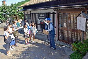 出入りを制限した鍋島藩の関所跡で説明を聞く子ども観光ガイド=伊万里市の大川内山