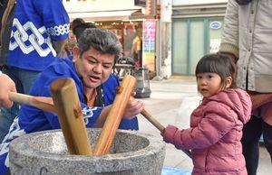 九電工佐賀支店の社員と餅つきをする児童ら=佐賀市の656広場