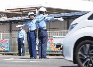 交差点の中央に立ち、手信号で車を誘導する鹿島署員=鹿島市の土井丸交差点