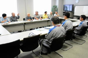 玄海町と唐津市鎮西町で実施された北部地区住民検診について質問する会議メンバー(奥)と回答する九電社員=玄海町の玄海エネルギーパーク