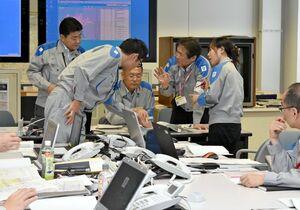 訓練で現場の状況を把握し、復旧に向けて話し合う社員=佐賀市の九州電力佐賀支社