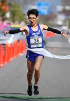 ハーフマラソン一般男子で優勝のゴールテープを切る橋本龍一(順天堂大)=鹿島市林業体育館前