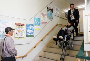 車いすに乗ったまま階段を上り下りできる昇降機の実演を見る福祉関係者ら=佐賀市の県在宅生活サポートセンター