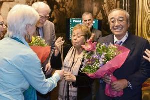 24日、バルセロナでの授賞式でメダルを受け取る「オール沖縄会議」の高里鈴代共同代表(中央)と、花束を受け取る安次富浩さん(右)(共同)
