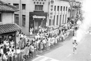 1964東京五輪聖火リレーの走者の写真。多くの住民が沿道で拍手している(近藤博昭さん所蔵、有田町教育委員会提供)