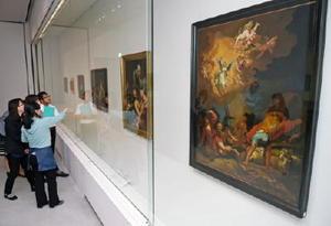 開幕を前に開かれた内覧会で作品を鑑賞する関係者たち=佐賀市の県立美術館