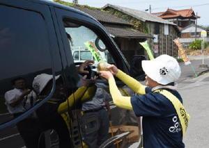 ドライバーに伊万里梨を渡し、交通安全を呼び掛ける参加者=伊万里市大川町
