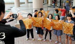完成したハンカチをカメラに向けて掲げる児童たち=嬉野市の嬉野小学校