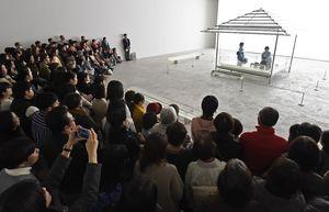 大勢の来場者の視線を一点に集め、ガラスの茶室で行われたお点前パフォーマンス=佐賀市の県立美術館