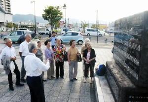 「ふるさとよ」の歌碑に集まり、合唱する伊万里高校の同窓生=JR伊万里駅前広場
