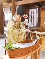 奉納されたブリに御神矢で切り目を入れる草場昭司宮司=佐賀市の佐嘉神社