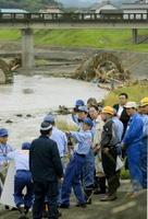 九州北部の豪雨でJR久大線の鉄橋が流失した現場を視察する安倍首相(中央)一行=12日午前、大分県日田市