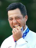 男子ゴルフで優勝し、金メダルをかむ米国のザンダー・シャウフェレ=霞ケ関CC