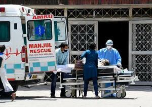 病院に搬送される、新型コロナウイルス感染者とみられる患者=18日、ニューデリー(共同)