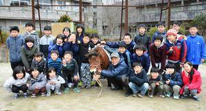 チャロと吉田孚さん(中央右)を囲み、記念写真に収まる児童たち=唐津市の大良小