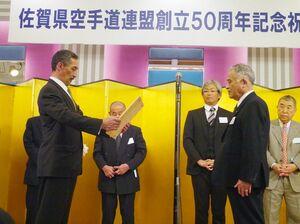 功労者らに表彰状を贈る鍋島直晶会長(左)=佐賀市のホテルニューオータニ佐賀