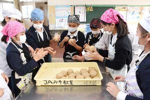 大豆とみそこうじを混ぜたものをソフトボール大に丸める子どもたち=みやき町の三根西小