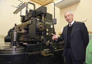 歯車を加工するため、昭和40年代から稼働する機械のそばで、竹内明太郎の足跡を語る唐津プレシジョン社長の竹尾啓助さん=唐津市二タ子の同社