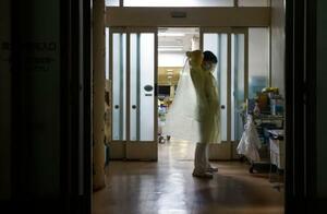 東京五輪開会式の当日、新型コロナの陽性者を診察するため、隔離された病室の前で防護服を着る看護師=23日夜、埼玉県川口市の埼玉協同病院