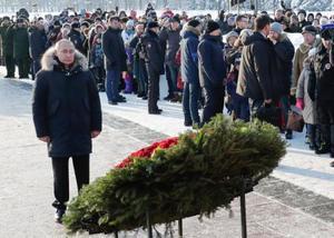 27日、レニングラード包囲の犠牲者が眠るロシア・サンクトペテルブルク郊外のピスカリョフ墓地を訪れ、献花するプーチン大統領(タス=共同)
