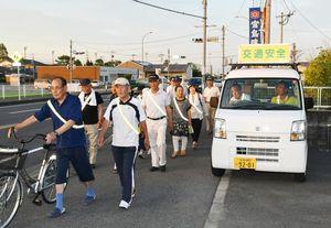 反射たすきをつけ、交通安全を呼び掛けながらパレードする巨勢町民=佐賀市巨勢町周辺