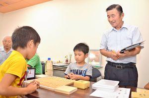 小学生向けの将棋入門教室を開いている内山博さん(右)=基山町の基山モール商店街まちなか公民館