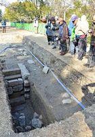 佐賀城本丸跡の発掘調査で見つかった石階段の遺構を見学する参加者たち=佐賀市城内