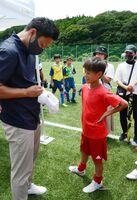 赤星さんからサインをもらう大坪少年の選手ら=佐賀市富士町の山村広場グラウンド